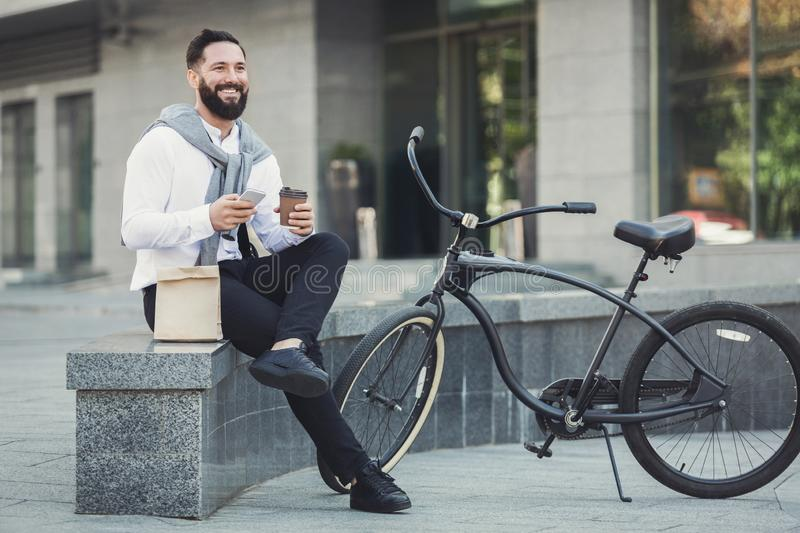 Young business man eating his lunch outdoors. Young businessman eating his lunch, having coffee break and using smartphone outdoors royalty free stock photography