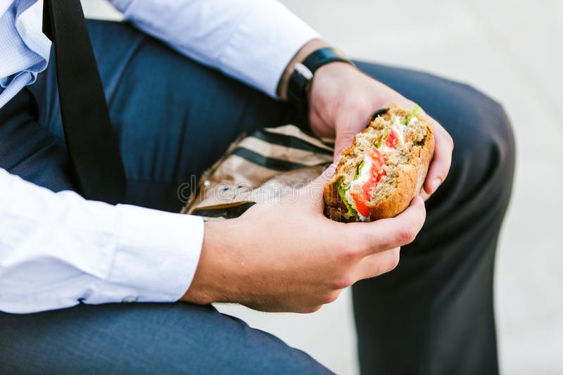 Young Business Man Eating Outdoor Sandwich for breakfast stock photo