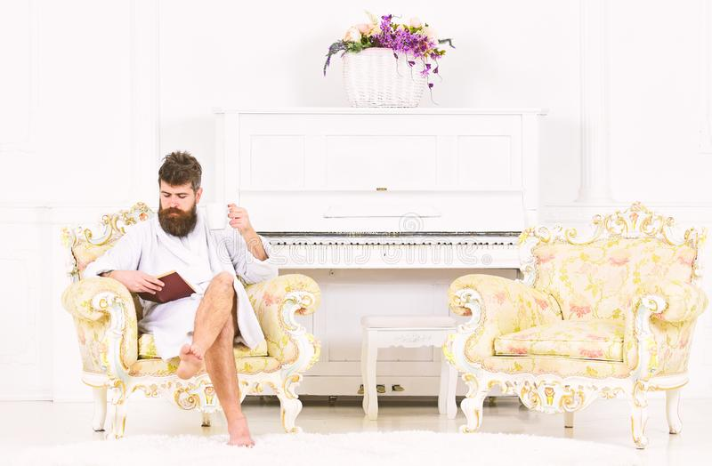 Young business man enjoying his morning coffee before work. Concentrated guy reading a book while sitting in armchair royalty free stock images