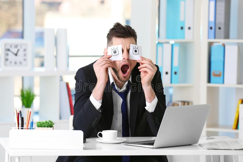 Young business man with fake eyes painted on paper stickers yawning at workplace stock photo