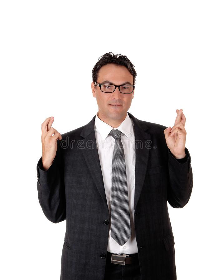 Young business man giving a sign with fingers crossed stock images