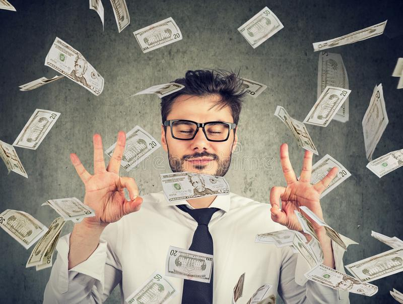 Business man meditating under money rain royalty free stock photos