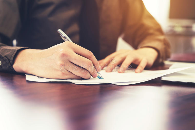 Young business man hand writing paper in the office with sunlight. Vintage toned filter. royalty free stock photos