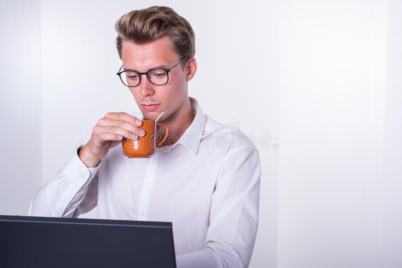 Young business man having a coffee while working with laptop stock photography