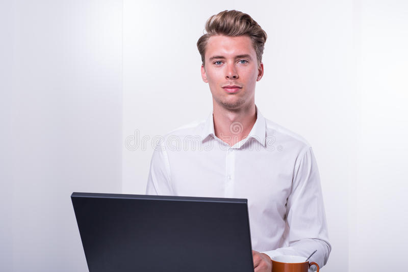 Young business man having a coffee while working with laptop royalty free stock image