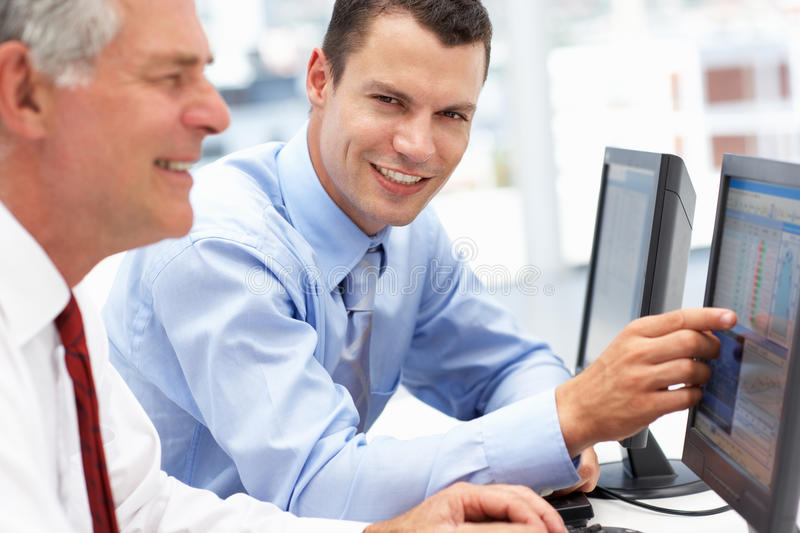 Young business man helping senior business man royalty free stock photo