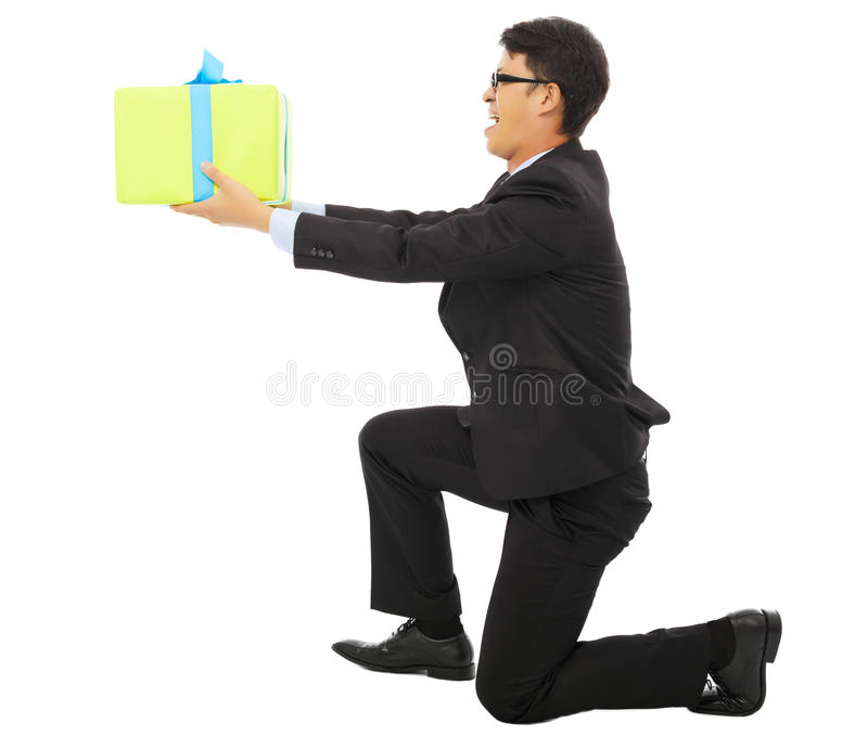 Young Business man holding a gift box and kneel. Isolated on white background stock photo