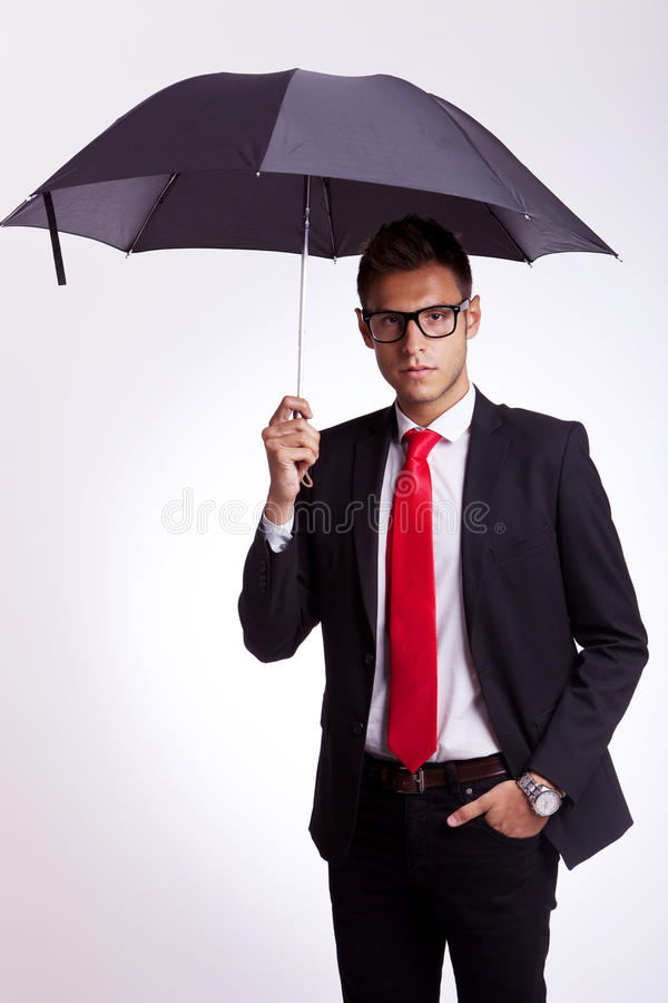 Young business man holding an umbrella royalty free stock images
