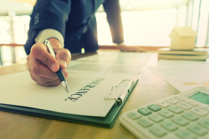 Young Business man insurance agent. Show document contract to the customer at the table in office stock image