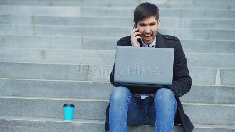 Young business man with laptop computer having stress after phone call and sitting on stairs in street. Businessman stock photography