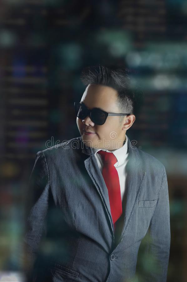 Young business man looking clever and smiling wearing suit, red tie, and sunglasses. royalty free stock image