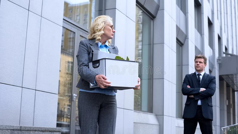 Young business man looking at dismissed aged lady leaving office, competition royalty free stock photo