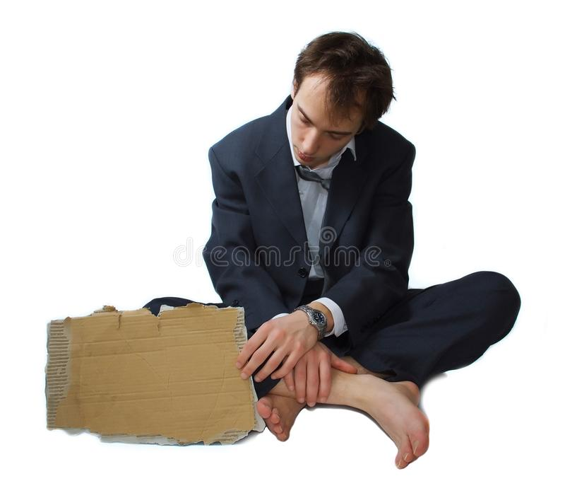 Young business man made redundant begs. On the street, looking at his sign stock photo