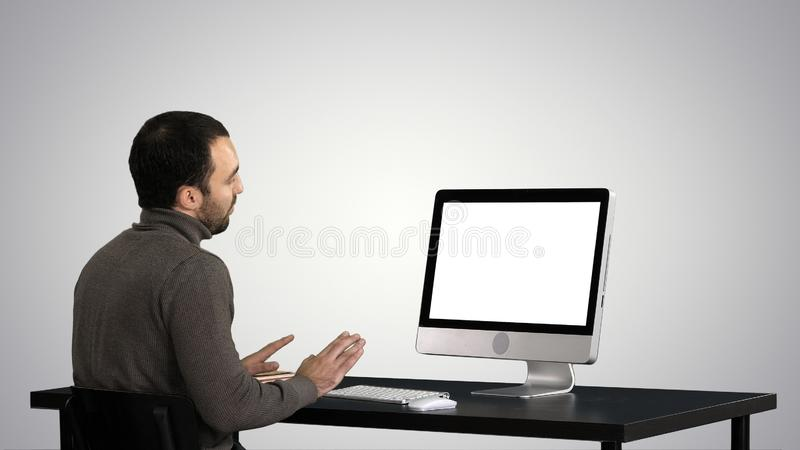 Young business man making video call on his computer on gradient background. royalty free stock image