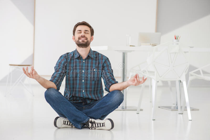 Young business man meditating stock photography