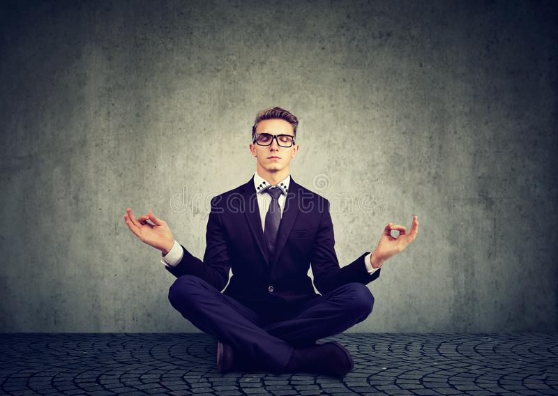 Young business man meditating relaxing with eyes closed royalty free stock photo