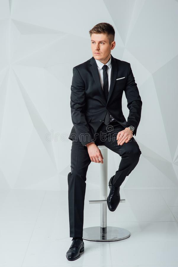 Young business man in modern suit sitting on chair. Side view picture of a young business man in elegant modern suit sitting on a chair and looks away from the royalty free stock image