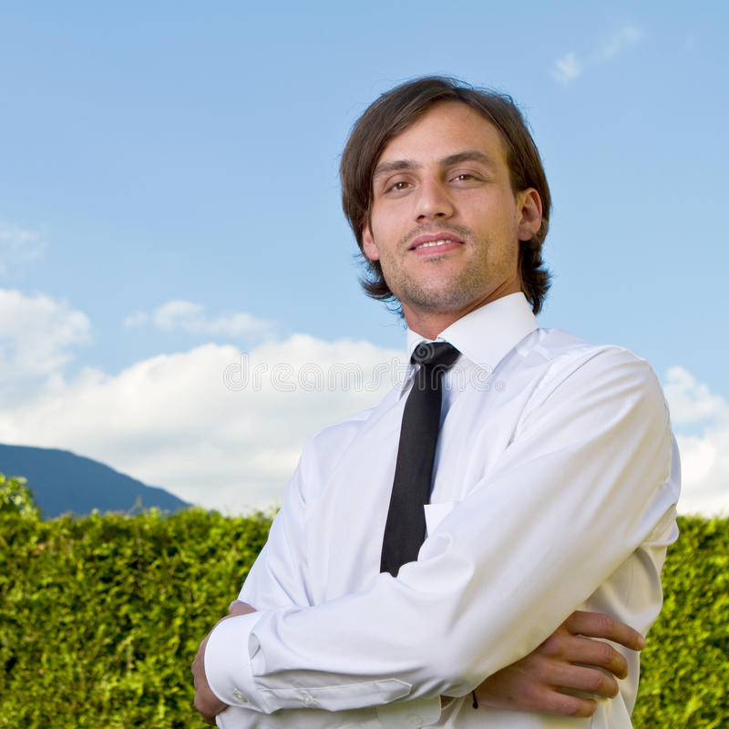 Young business man over blue sky. Young businessman with longer hair over a blue sky outside stock images