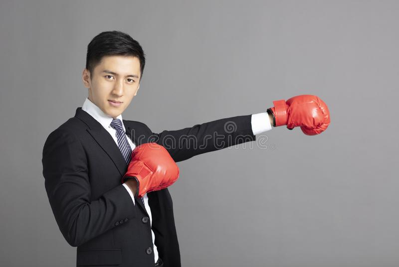 Business man ready to fight with boxing gloves. Young Business man ready to fight with boxing gloves royalty free stock photo