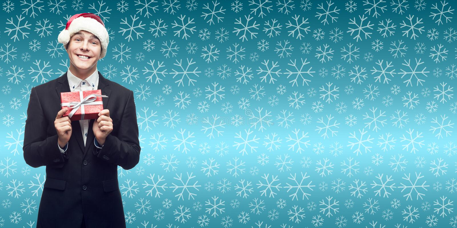 young business man in santa hat holding christmas gift over winter background royalty free stock image