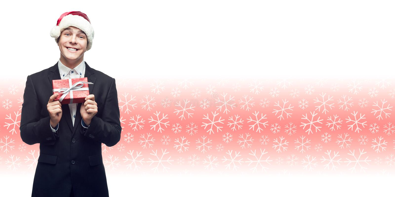 young business man in santa hat holding christmas gift over winter background stock image