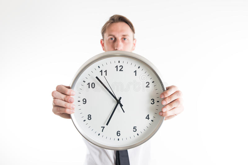 Young business man showing a big clock royalty free stock photos