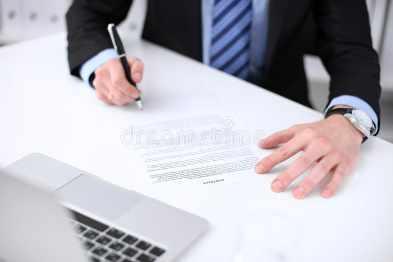 Young business man signs contract while sitting at the desk in office, close up of hands royalty free stock photos