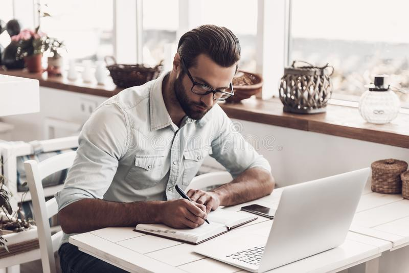 Young Business Man Sitting in Cafe taking Notes royalty free stock photos