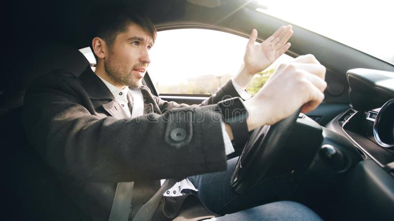 Young business man driving car very upset and stressed after hard failure and moving in traffic jam stock images