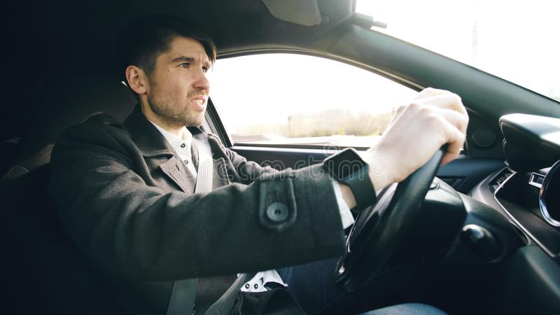Young business man driving car very upset and stressed after hard failure and moving in traffic jam. Young business man sitting in car very upset and stressed royalty free stock images