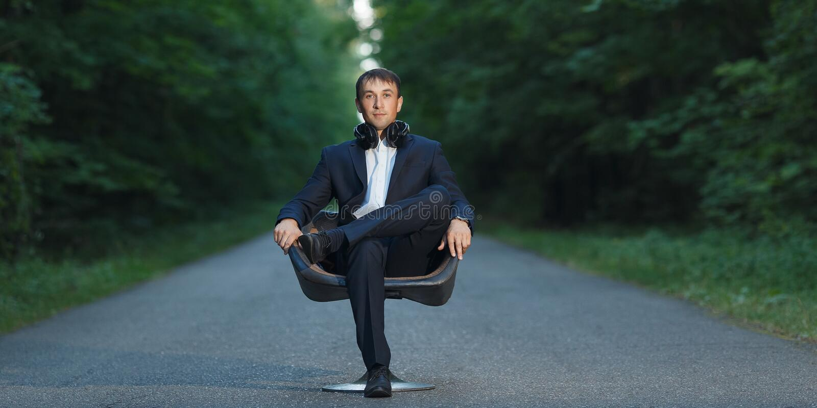 Young business man sitting on chair in suit and headphones in forest royalty free stock photo