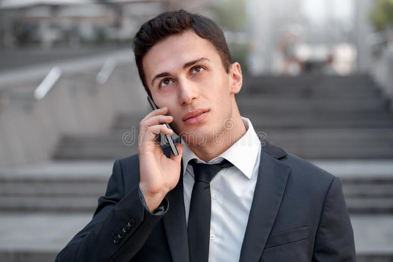 Business lifestyle. Businessman standing on the city street talking on smartphone pensive close-up stock image