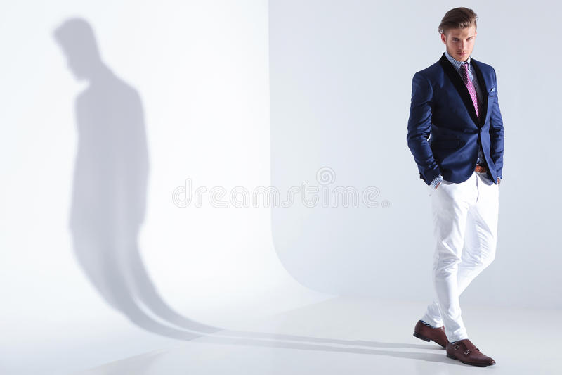 Young business man stands with both hands in pockets royalty free stock image