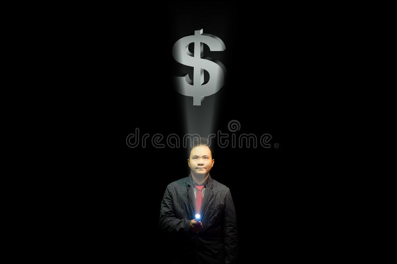 Young business man in suit pointing a flashlight to a dollar sign. Searching for money concept. stock images