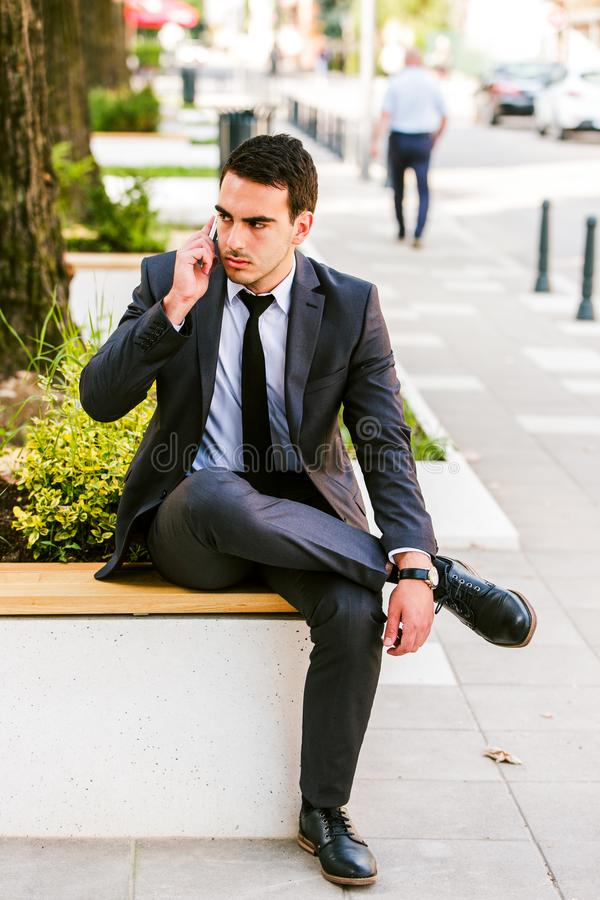 Young Business Man Talking At Phone While Sitting Outdoor royalty free stock photos