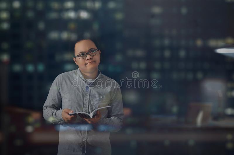 Young business man temporarily looking at something else and thinking and analyzing an idea while reading and holding a book. stock image