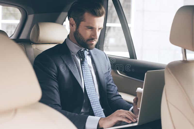 Young business man test drive new car. Young business person test drive new vehicle drinking coffee royalty free stock image