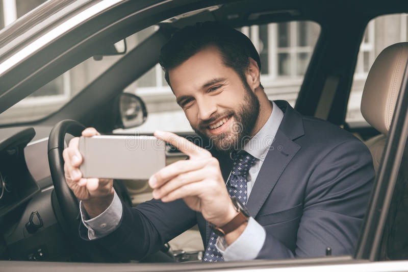 Young business man test drive new car. Young business person test drive new vehicle using digital device stock images