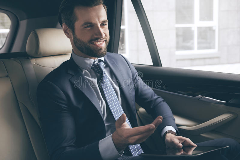 Young business man test drive new car. Young business person test drive new vehicle usng digital device royalty free stock photography