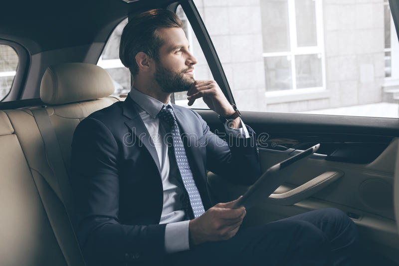 Young business man test drive new car. Young business person test drive new vehicle usng digital device royalty free stock photos