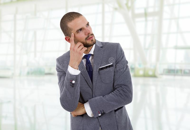 Business man. Young business man thinking at the office stock image