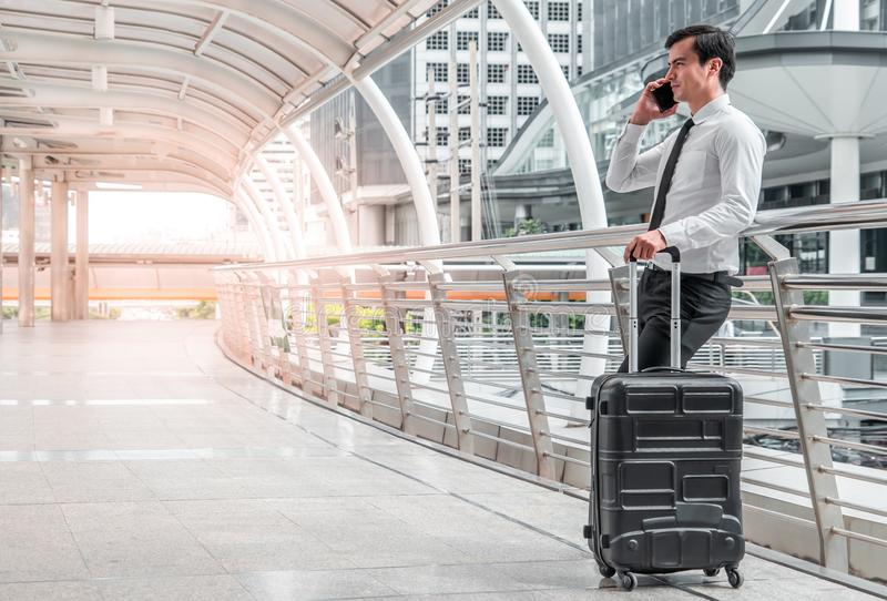 Business man man on business trip standing with his luggage and making a call outside airport. Business traveler making. Young business man man on business trip stock image