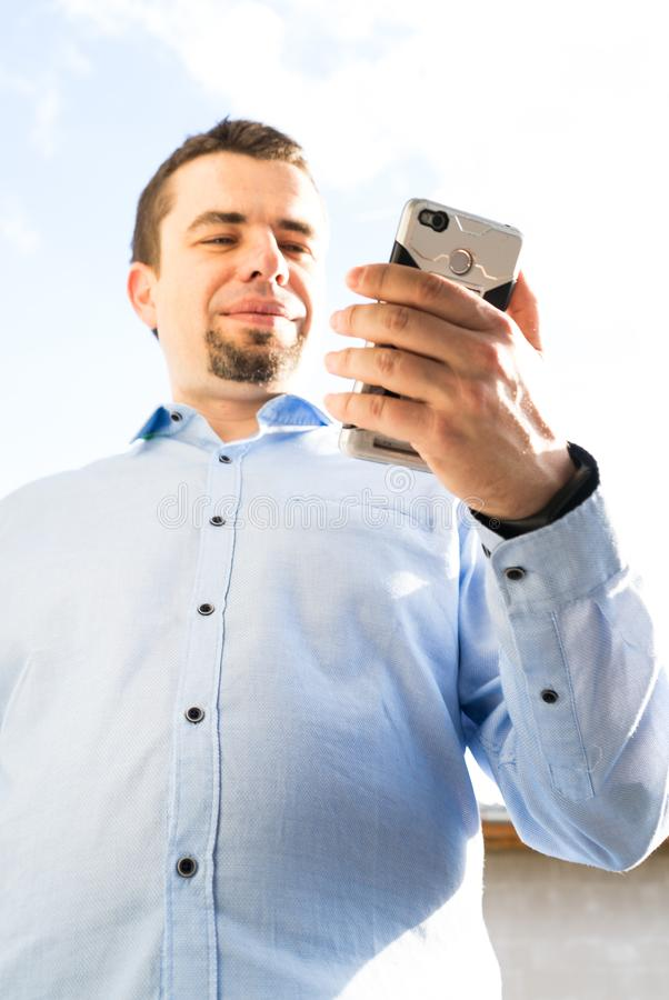 Young business man using cellphone laughing and typing message stock photo