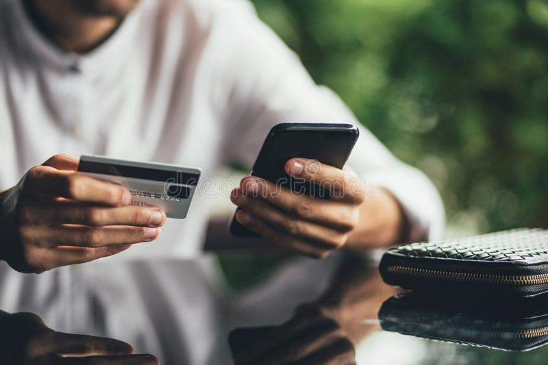Young business man using credit card shopping online in coffee shop cafe. close up stock images