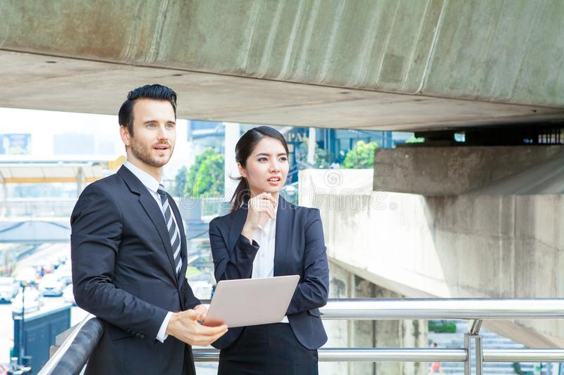 Young business Man and woman working together on a laptop outdoors in modern city. Portrait of a woman and a man in front of a la. Young business Man and women royalty free stock photo