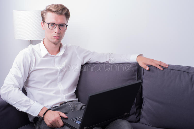 Young business man working at home on couch.  royalty free stock images