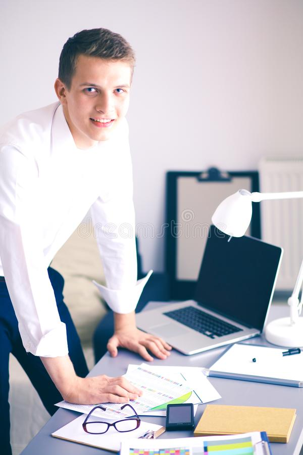 Young business man working in office ,standing . Young business man.  royalty free stock image