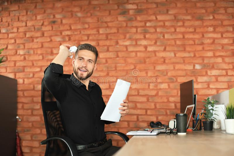 Young business man is working with papers while sitting in the office stock photography