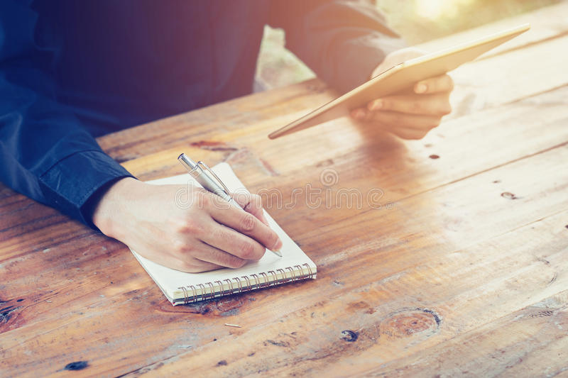 Young business man writing note pad and using tablet in coffee s. Hop witn vintage filter royalty free stock photography