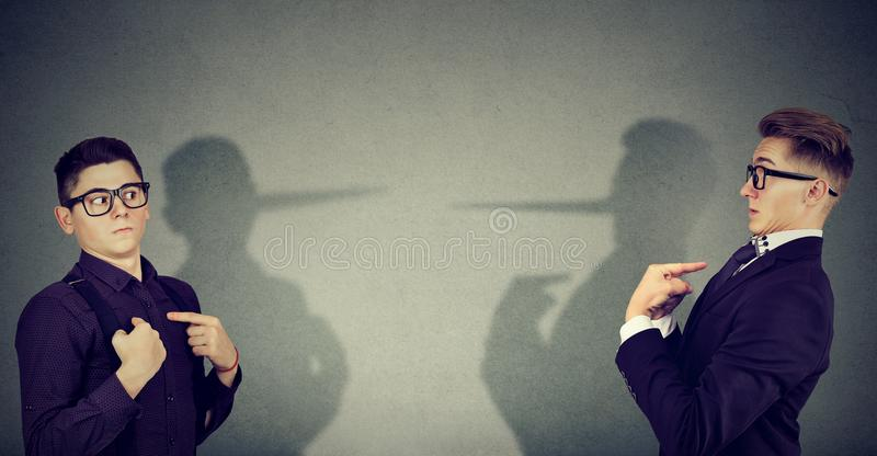 Liars men blaming each other. Young business men pretending and blaming each other in lie royalty free stock photography